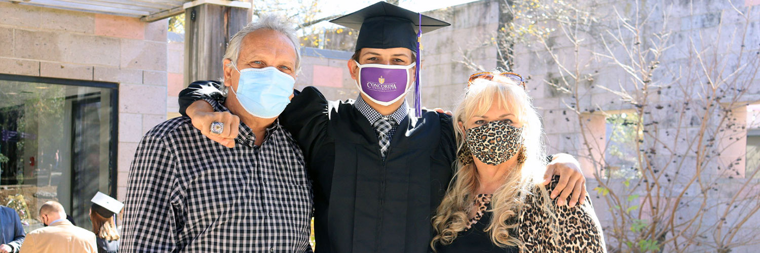 CTX graduate with parents at commencement
